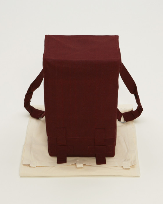 A rectangular object with two straps toward the back is wrapped in red fabric and placed above a folded beige muslin.