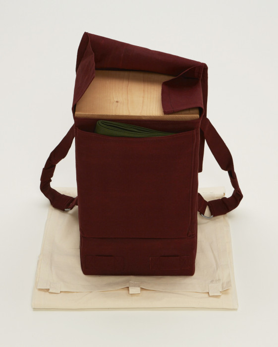 A rectangular object with two straps is wrapped in red fabric and placed above beige muslin. The objectÕs top flap is open, revealing a wooden slab and folded green cloth.