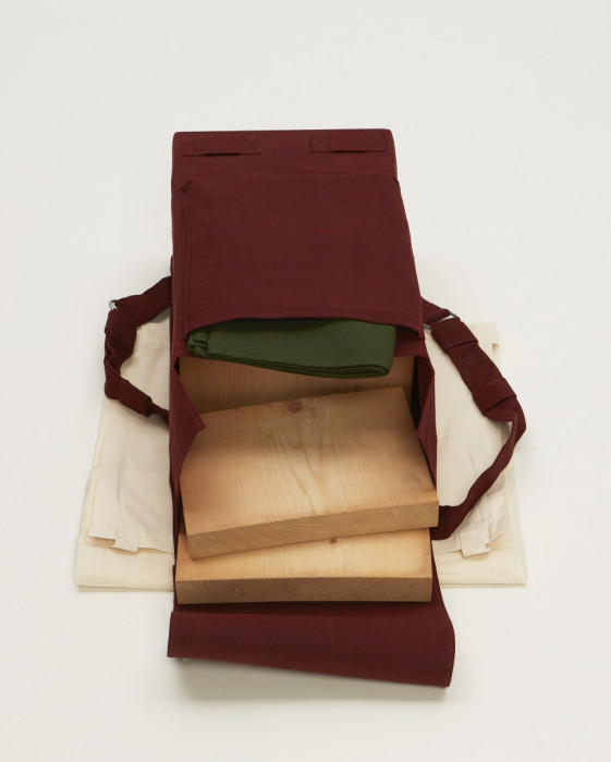 A rectangular object with two straps is wrapped in red fabric and placed above beige muslin. The objectÕs top flap is open, revealing three wooden slabs and a green cloth.