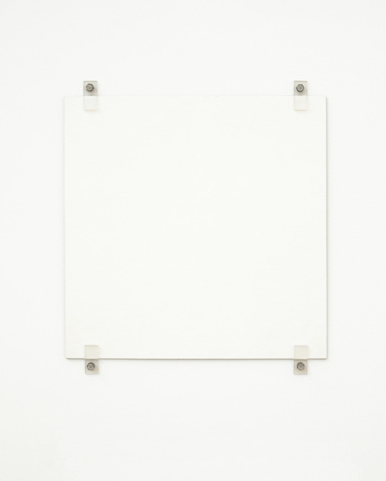 A white square hangs on a white wall using four exposed fasteners with bolts, two on the top and two on the bottom.
