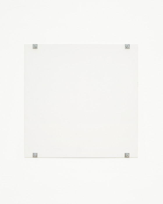 A white square hangs on a white wall using four gray bolts and fasteners, affixed to the bottom and top of the work and near the corners.