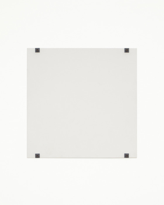 A white square hangs on a white wall using four black bolts and fasteners, affixed to the bottom and top of the work and near the corners.