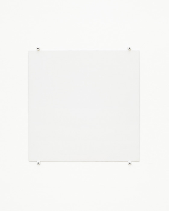 A white square hangs on a white wall using four white bolts and fasteners, affixed to the bottom and top of the work and near the corners.