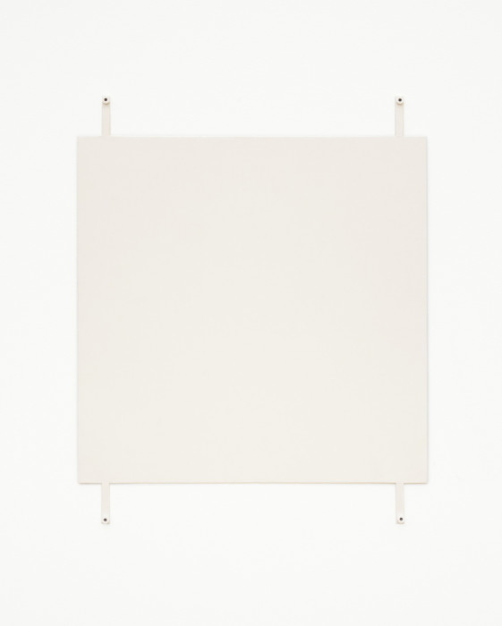 A off-white square hangs on a white wall using four exposed fasteners with white bolts, affixed to the bottom and top of the work and near the corners.