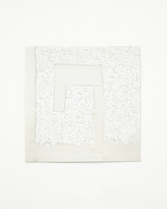A white square with an angular central spiral hangs on a white wall. Rectangular sections of smooth white paint interrupt rough swathes of brushstrokes.