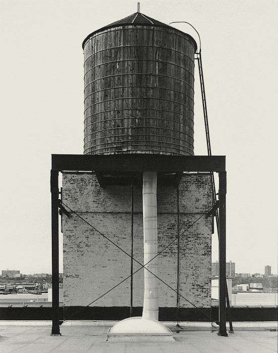 Black-and-white photograph of a rooftop water tower above a small brick penthouse surrounded by metal supports
