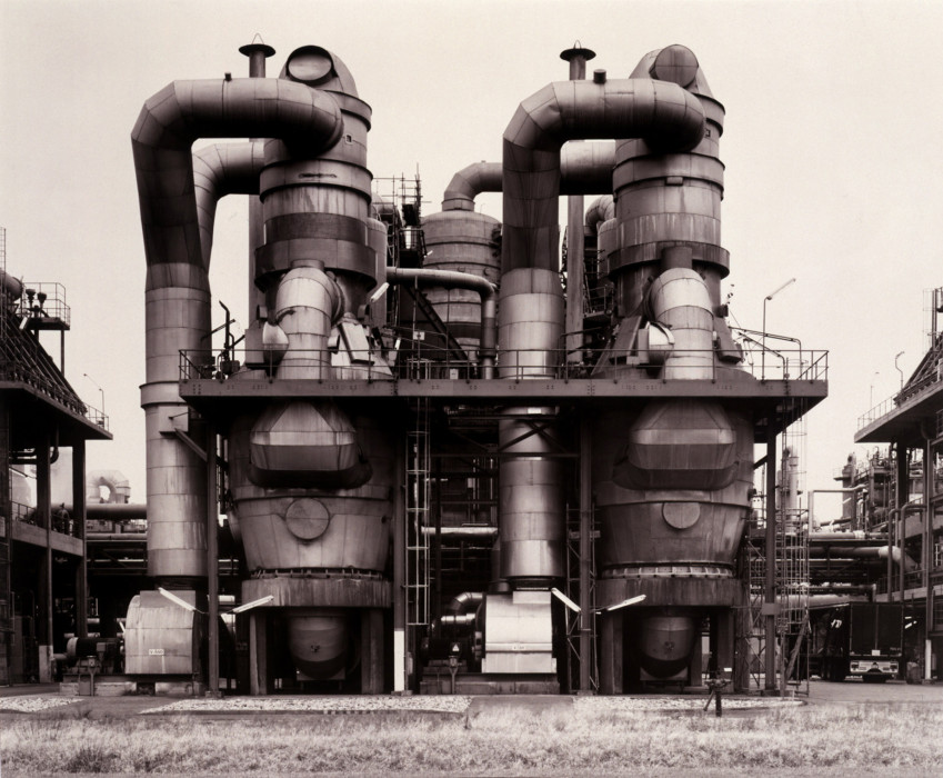 Black-and-white photograph of factory with curving cylindrical tubes, tanks, and other protuberances