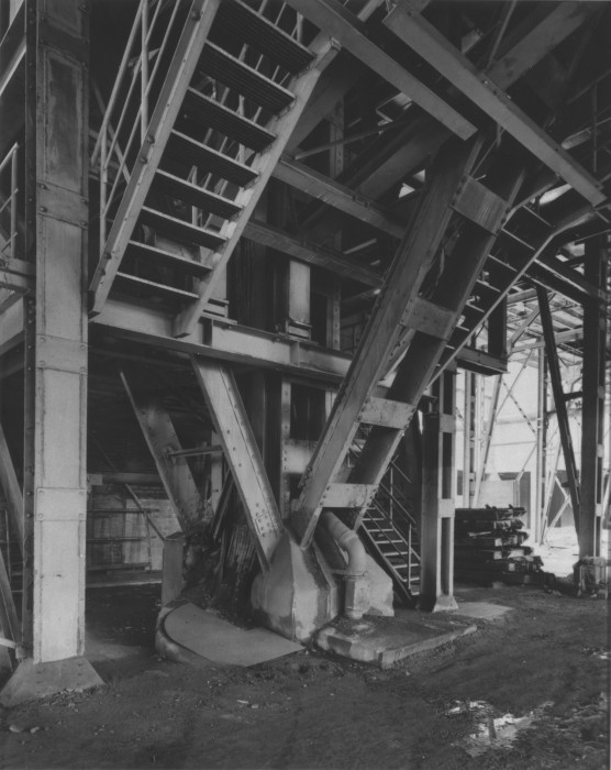 Black-and-white photograph, taken at an angle, of the underside of a staircase and other diagonal building supports.