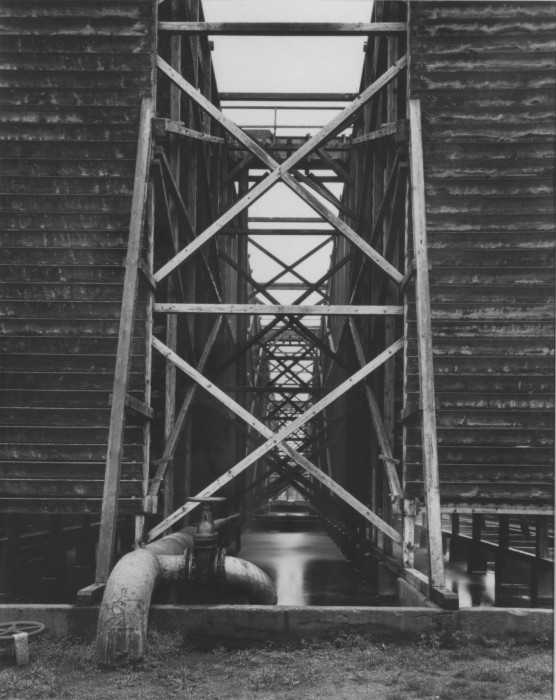 Black-and-white photograph of two building structures on stilts above a pool of liquid flanking an open central passageway filled with sets of diagonal crossbeams extending into the background.