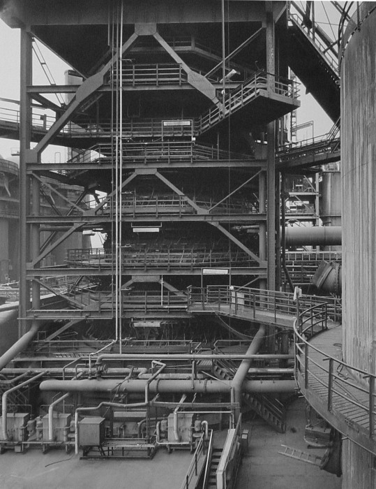 Black-and-white photograph of outdoor tiered metal structure with multilevel railings and walkways and large cylindrical pipes connecting to other structures.