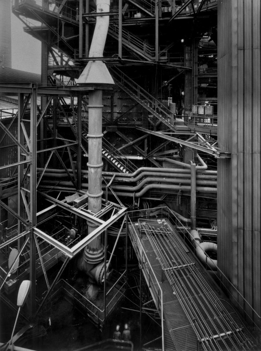 Black-and-white photograph of a factory setting with numerous sets of pipes, support beams, and staircases.