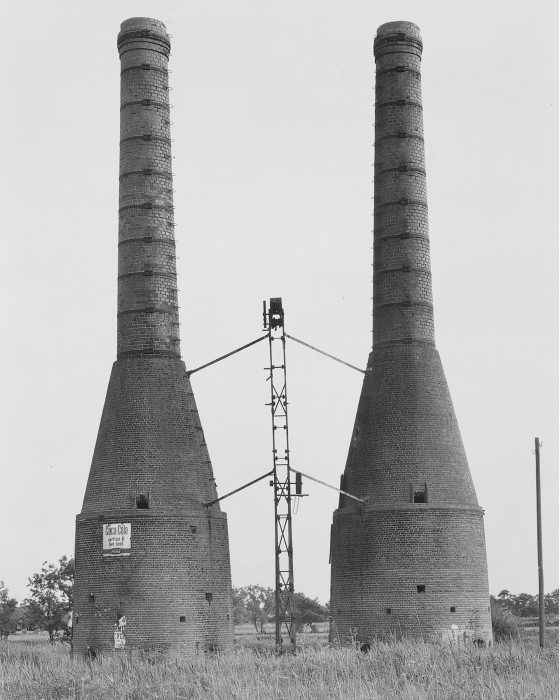 Black-and-white photograph of two brick towers with thick cylindrical bases, conical mid-sections, and thin cylindrical tops.