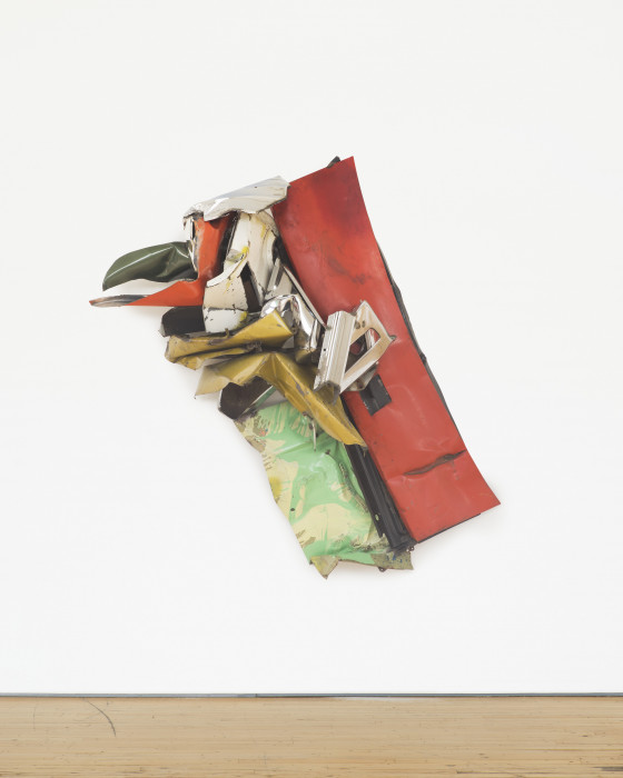 A diagonally mounted sculpture made red, yellow, green, and white metal parts hangs on a white wall.