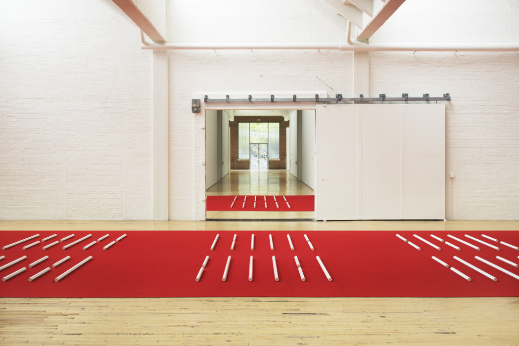 A series of white hexagonal poles laid horizontally on a red carpet.
