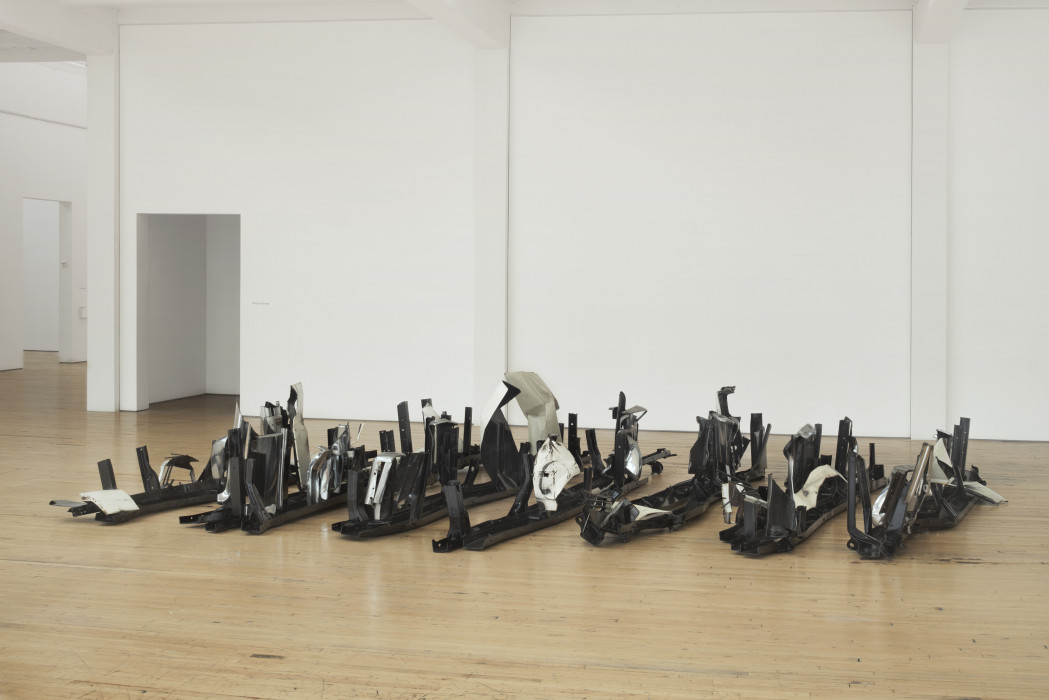 A series of long, spiky, black, metal sculptures are arranged in parallel lines on a wooden floor.