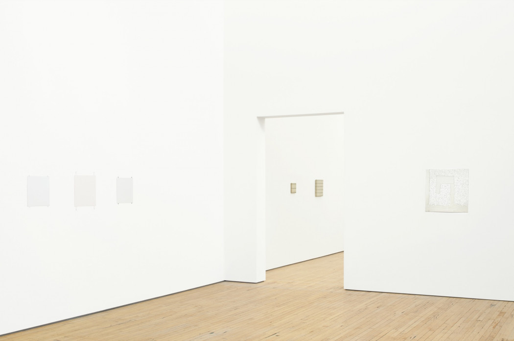 Six small paintings hang on white walls above a wood floor. Three whites paintings are on a wall to the left, one white painting is on a wall to the right, and two tan paintings are visible through a doorway in the center.