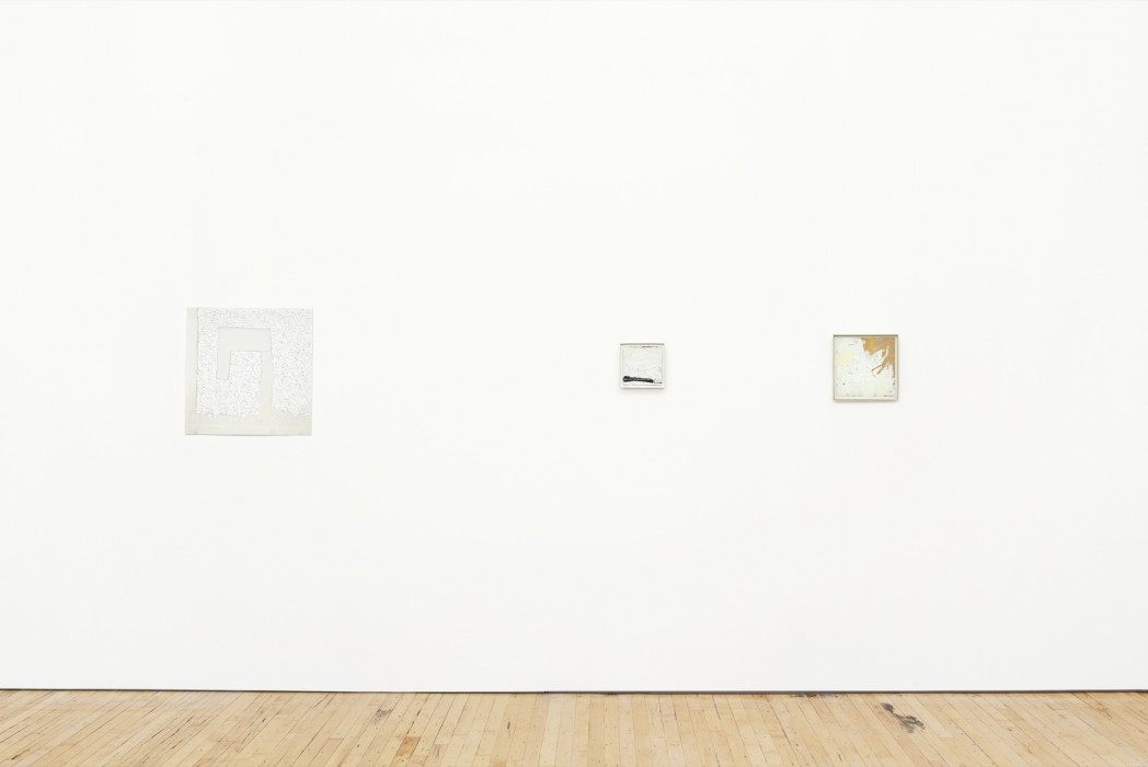 Three small, square white paintings hang on a white wall above a wood floor.