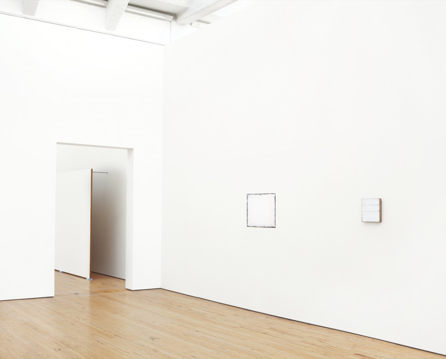 Two square white paintings hang on either side of a corner; the left one is very large and the right one is very small. A large, rectangular white painting affixed to a wall by long metal rods and resting on the wood floor is partially visible through a doorway to the left of the paintings.