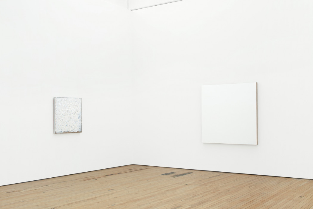 Two square white painting hang on walls above a wood floor on either side of a corner. The right one is large, and the left one is small.