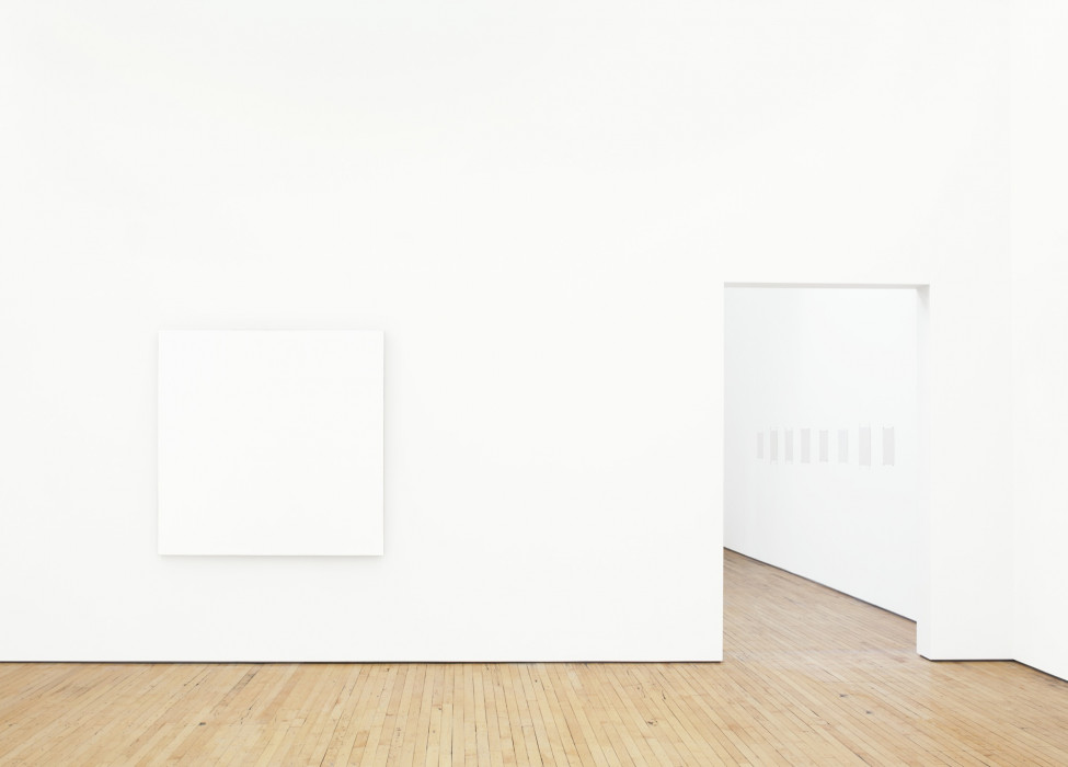 A large, square white painting hangs on a white wall above a wood floor. Eight small, square white paintings are visible through a doorway to the right.