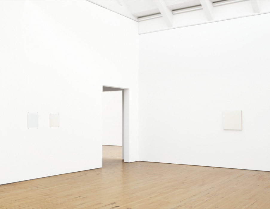 Three small, square white paintings hang on either side of a corner between which is a doorway. The two on the left wall are affixed with fasteners and bolts. The canvas of the larger painting on the right is visible on its right side.