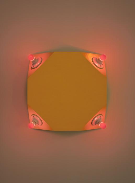 A warped yellow metal square with a red lightbulb in each corner is mounted on a wall.