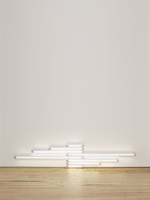 Fluorescent white tubes of various lengths installed against a white wall close to the wood floor.