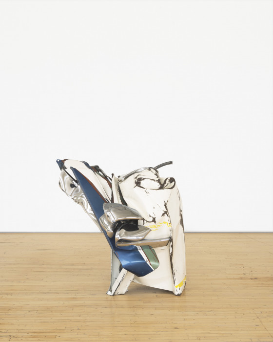 A squat sculpture made of chrome, white, and blue metal parts that twist together rests on a wooden floor.