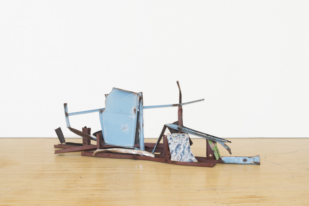 A horizontally oriented, long sculpture made of blue, red, and multicolored metal parts rests on a wooden floor.