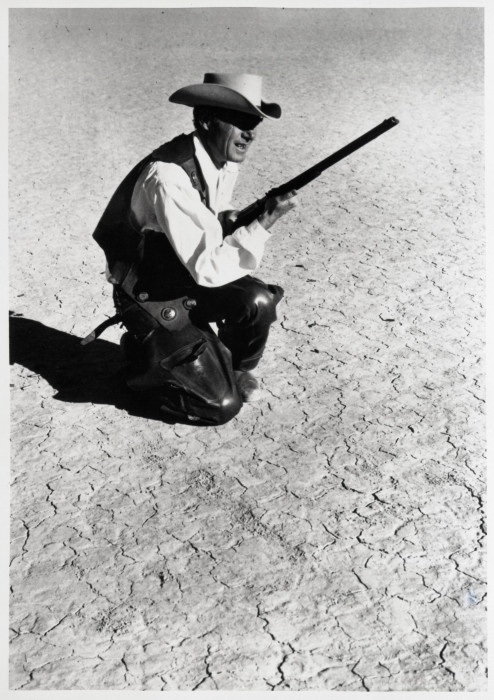 A cowboy holds a shotgun and kneels on a barren desert floor in this black-and-white film still.