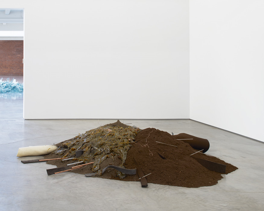 A pile of dirt and moss is strewn with strips of felt and metal rods above a cement floor.