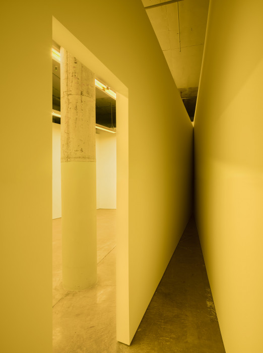 A doorway frames a column and two walls intersecting at a narrow angle, all bathed in yellow fluorescent light.