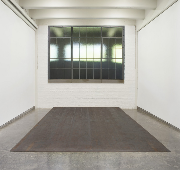 Room with window, white walls, and slightly slanted, steel slab resting on cement floor
