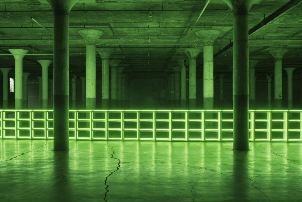 Green fluorescent barrier spans a large dark room with pillars.