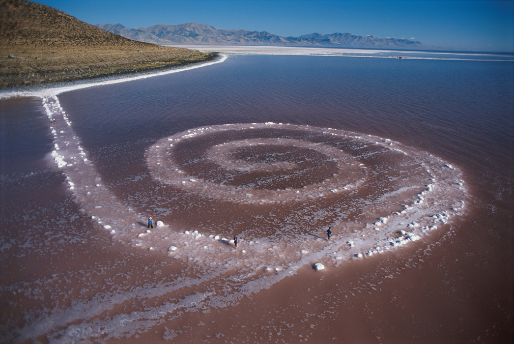 An aerial view of a large spiral made of rocks that runs counterclockwise from the shore into a pink lake.