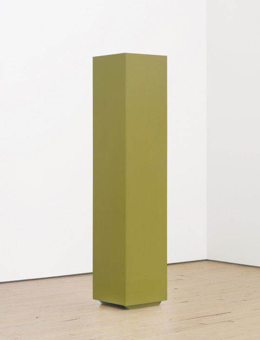 A tall, green column is placed on a wooden floor in front of two white walls.