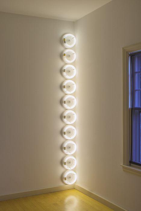 Ten circular, white, fluorescent lightbulbs are placed vertically in the corner of a room.