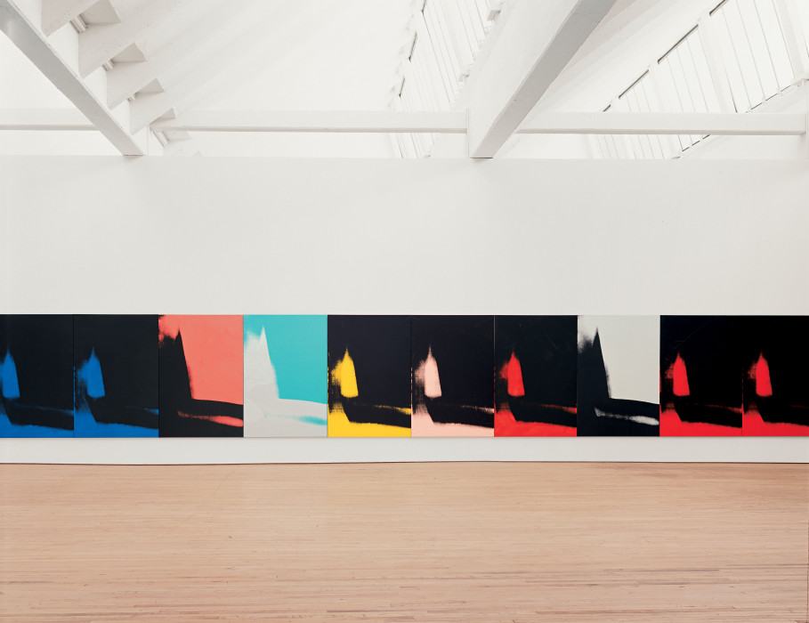 Ten canvases hang edge to edge and low to the floor. Each canvas features an identical abstract mark painted in black, gray, red, green, yellow, peach, or blue.
