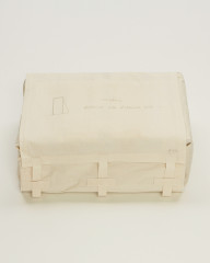 A rectangular object is wrapped in beige fabric. A shape with