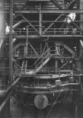 Black-and-white photograph of a tiered metal structure with tubes, railings, and a staircase surrounding a blast furnace.