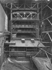 Black-and-white photograph of a tiered metal structure with railings, platforms, and diagonal support beams.