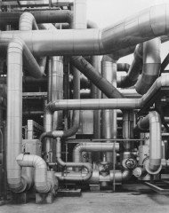 Black-and-white photograph of coiled and intersecting tubes of various sizes.