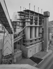Black-and-white photograph of a windowless building below eight cylindrical towers, topped with scaffolding and tall ventilation tubes within a larger industrial complex.