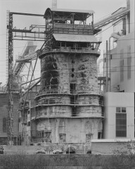 Black-and-white photograph of two interconnected towers atop a smaller building and below an open-air tiered structure within a larger industrial setting.