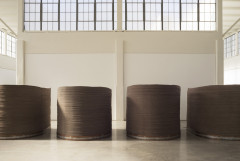 Four stacks of circular pieces of felt atop circular copper and iron base.