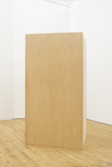 A wooden rectangular box is vertically placed on a wooden floor in a white room.