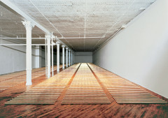 Five vertical columns of sections of brass rods on a wood floor.