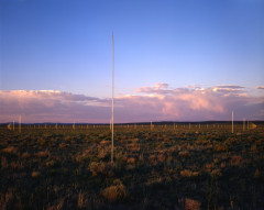 Tall silver poles sticking up out of a grassy landscape, with purple storm clouds in the sky.