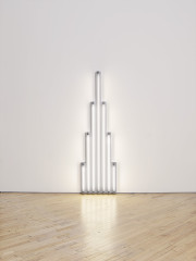 White fluorescent tubes mounted on a wall in the shape of a tower.