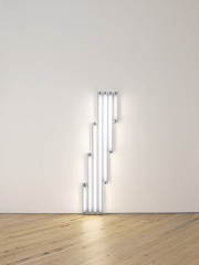 Seven fluorescent-white, tubular lights positioned against a white wall at varying heights beginning with the shortest bulb.